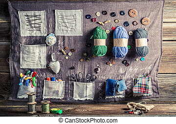 Vintage sewing mat made of threads, needles and buttons in...