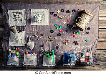 Old sewing cloth made of threads, needles and buttons in...