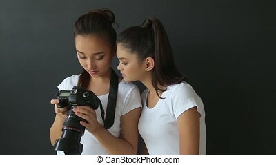 Two girls watch photos on the camera