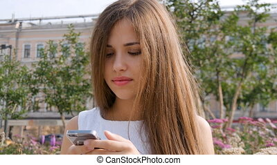 Attractive girl using mobile phone in a city. - Attractive...