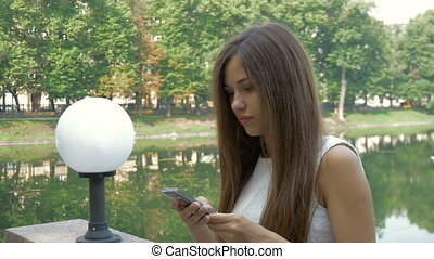 Attractive girl using mobile phone in a city. Smiling...