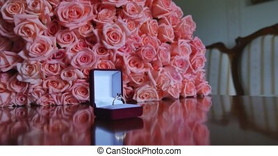 Red velvet box with golden ring and bouquet of pink roses
