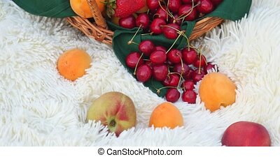 Basket of fresh organic fruits on white carpet.