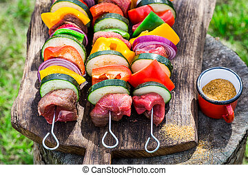 Fresh red meat and vegetables with herbs on grill
