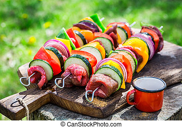 Fresh vegetables and red beef with spices on grill