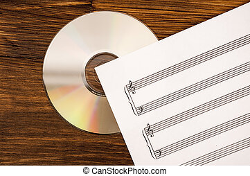 Music sheet and CD drive on wooden background. Old and new technology in music.