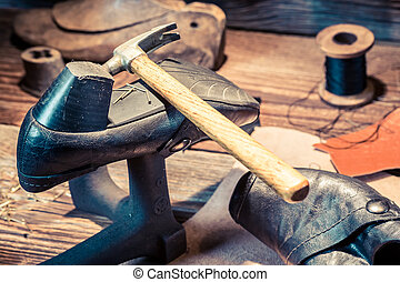 Vintage shoemaker workshop with brush and shoes