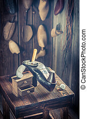 Aged shoemaker workshop with tools, leather and shoes