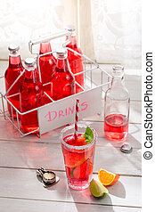 Tasty red summer drink in bottle with mint leaf
