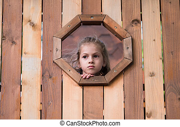 little girl looks out the window in a wooden house