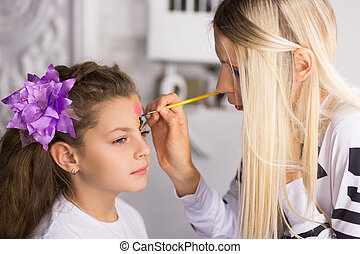 Woman paints the face of a girl
