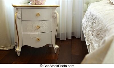 Beautiful white wedding flowers on the white vintage bedside...
