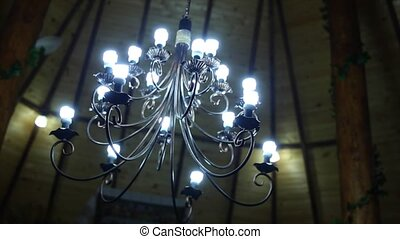 metallic chandelier on wood background.