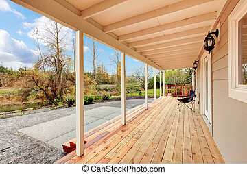 Covered wooden deck in the back yard with autumn landscape.