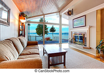Awesome living room interior with sloped wooden ceiling and water view.