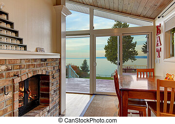 Small dining area with brick fireplace  and water view.