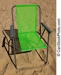Green folding camp chair standing on a sand
