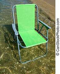 Green folding camp chair standing in water near the beach