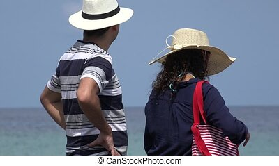 Tourist Couple Looking At Ocean Or Sea