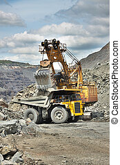 Iron ore mining - excavator is loading the dump truck on the...