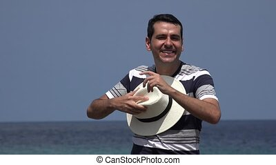 Man Dancing With Hat Near Ocean On Summer Vacation