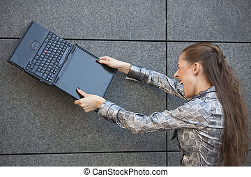 crushing laptop against wall - angry woman smashing a laptop...