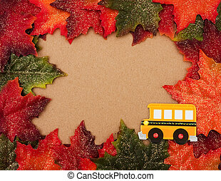 Back to school - Fall leaves making a border on a beige...