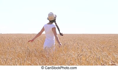 Young woman in white dress walking in a field of wheat -...