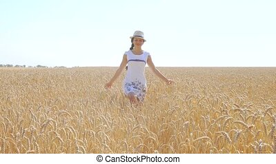 Young woman in white dress walking in a field of wheat