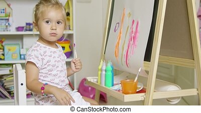 Pretty little girl artist sitting at an easel painting a...