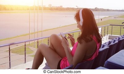 The girl with the phone and headphones at sunset HD