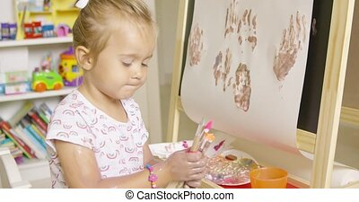 Cute little girl choosing a paint brush from a selection...