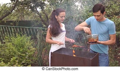 couple near the barbecue. - young woman and man near the...