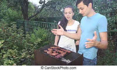 couple near the barbecue - young woman and man near the...