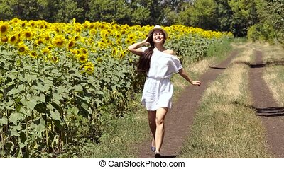 woman runs across the road near a field of sunflowers -...