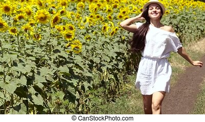 woman runs across the road near a field of sunflowers