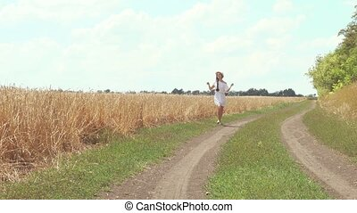 woman in a white dress runs across the road - young woman in...