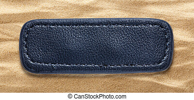 Blue blank leather label on sand background