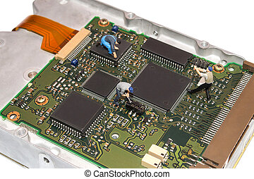 Miniature people repairing the hard drive. A broken computer...