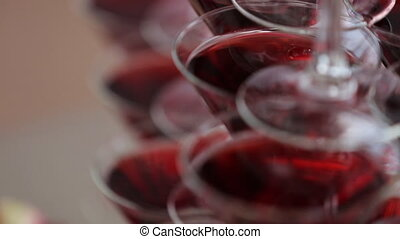 Triangular wineglasses, filled with red wine, stand on table...