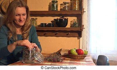 Herbalist woman put dried marjoram herbs on wooden shelf. 4K...