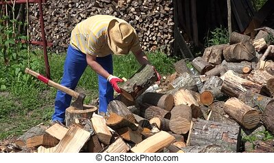 Villager man with old axe chops wood. 4K - Villager man with...