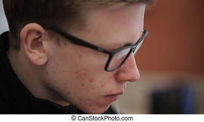 Young man in black-rimmed glasses with a serious face...