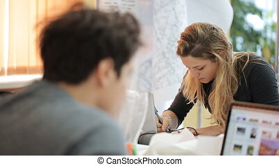 Young woman draws a on table, a student cartographer viewing...