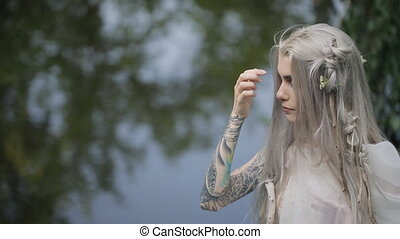Beautiful model takes part in photo session on lake shore....