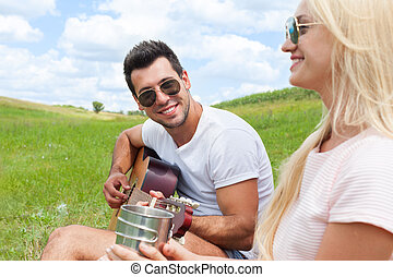 Young man playing guitar to his girl summer day couple love...