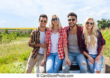 Friends sitting on car outdoor countryside people smile...