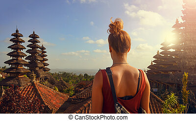 Young woman visits hinduism temple in Bali Besakih Temple -...
