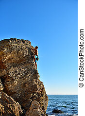 Young man climbing up on yellow mountain
