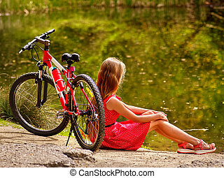 Bikes cycling girl into park sits leaning bicycle on shore -...